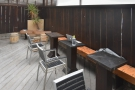 ... while a wooden bench with three small, rectangular tables runs along the back wall.