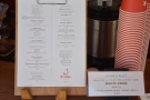The menu and coffee choices are on the clipboard left of the till, along with the...