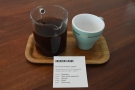 ... served in a carafe with a cup on the side, presented on a tray with an information card.