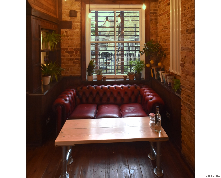 Beyond the booths, there's a coffee table and this cosy sofa under a window at the back.