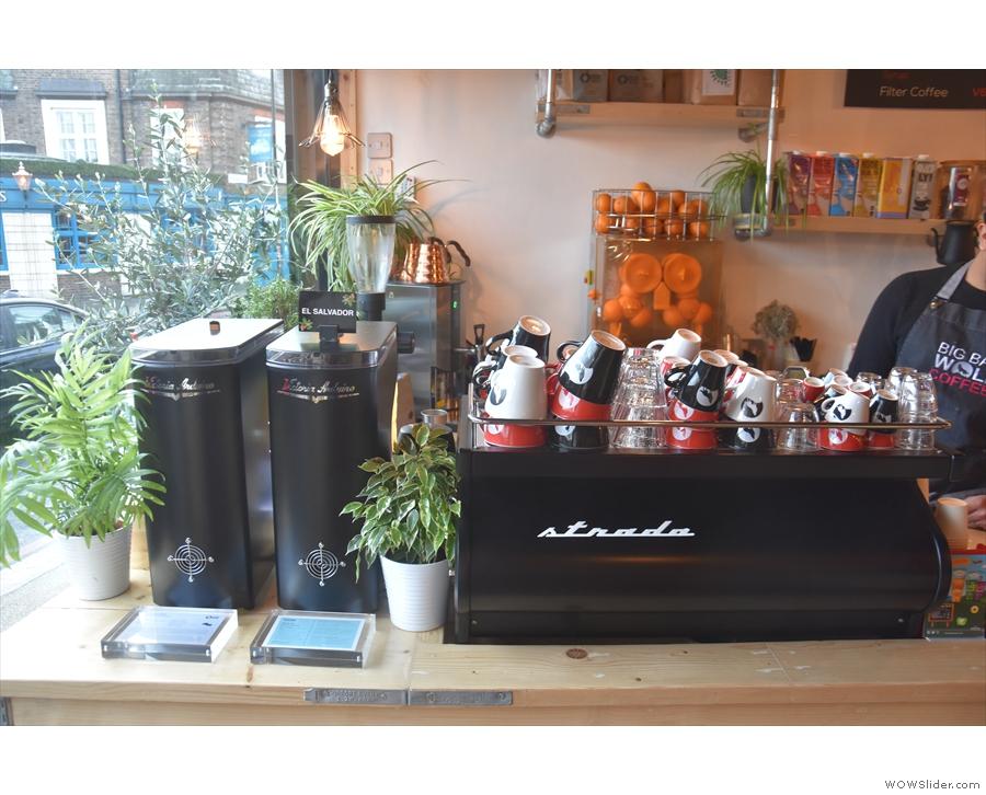 The espresso machine, a La Marzocco Strada, is at the front end of the counter.