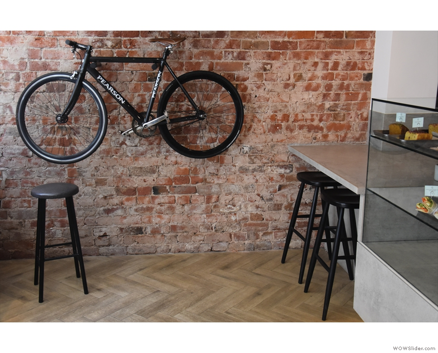 There's also a bicycle on the wall and, to the right of that, a pair of stools at the top...