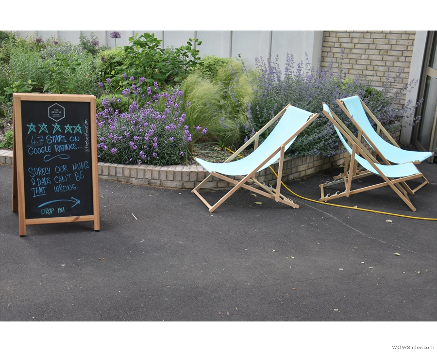 ... while on the other side of the path, there are three deck chairs and an A-board.