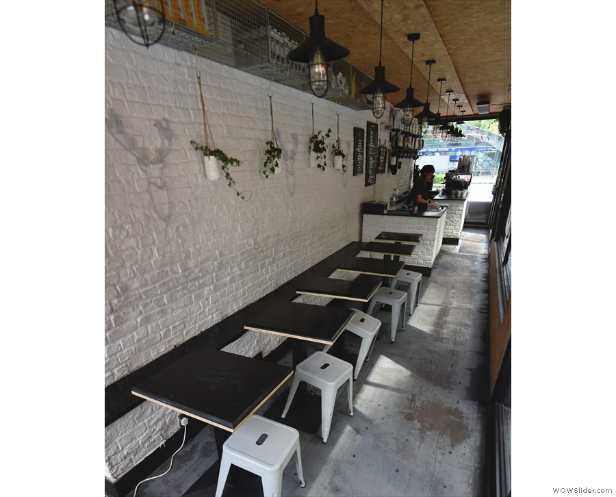 ... which leads into a cosy indoor seating area with a bench and six tables.