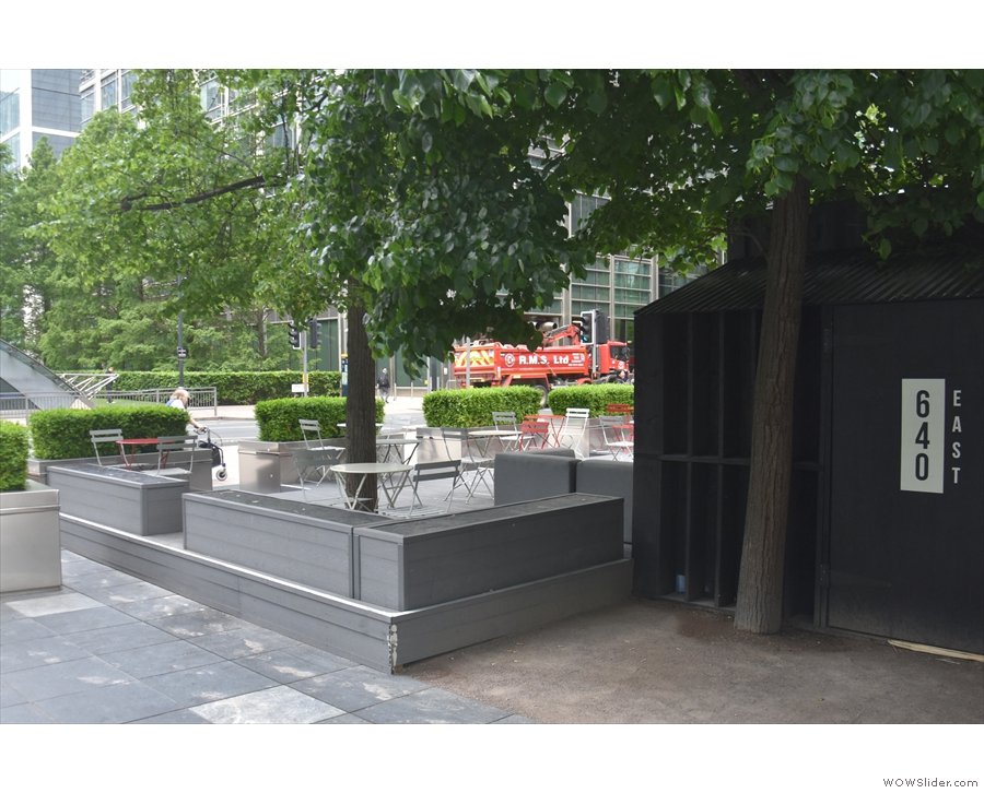 The outside seating is on a slightly raised decking area, screened by planters.