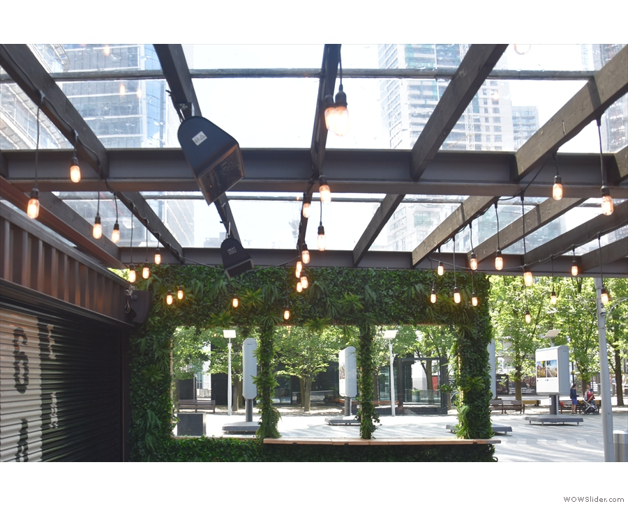 There are plenty of light bulbs hanging from the glass roof in the covered courtyard.