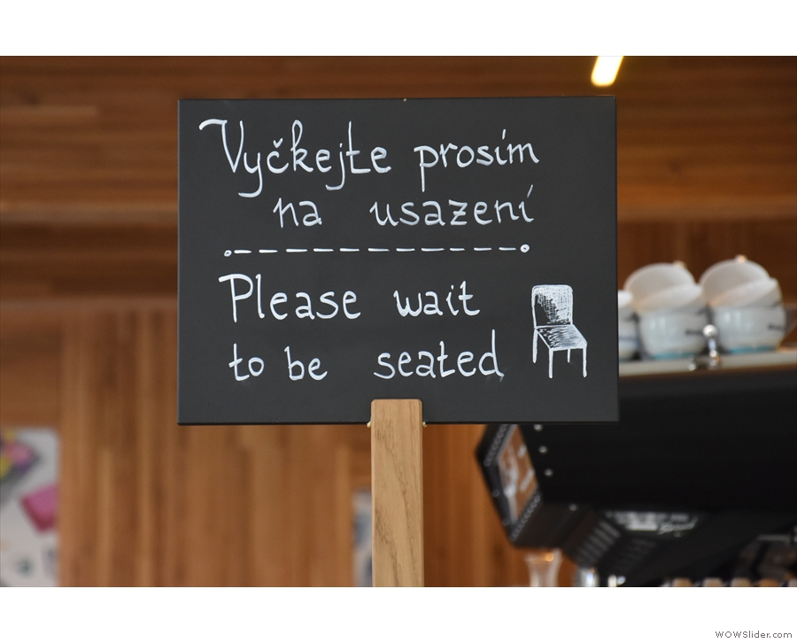 A handy sign at the top tells you to wait to be seated in English as well as Czech.