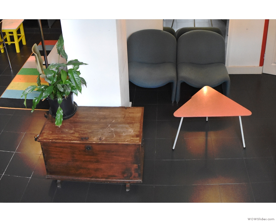 ... there's a pair of padded chairs and a triangular table opposite the bottom of the stairs.