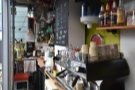 A closer look at the La Marzocco FB80 espresso machine, beyond which is a small kitchen.