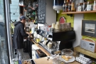 If you stand inside at the counter, you get a great view. First step, grind, then tamp.