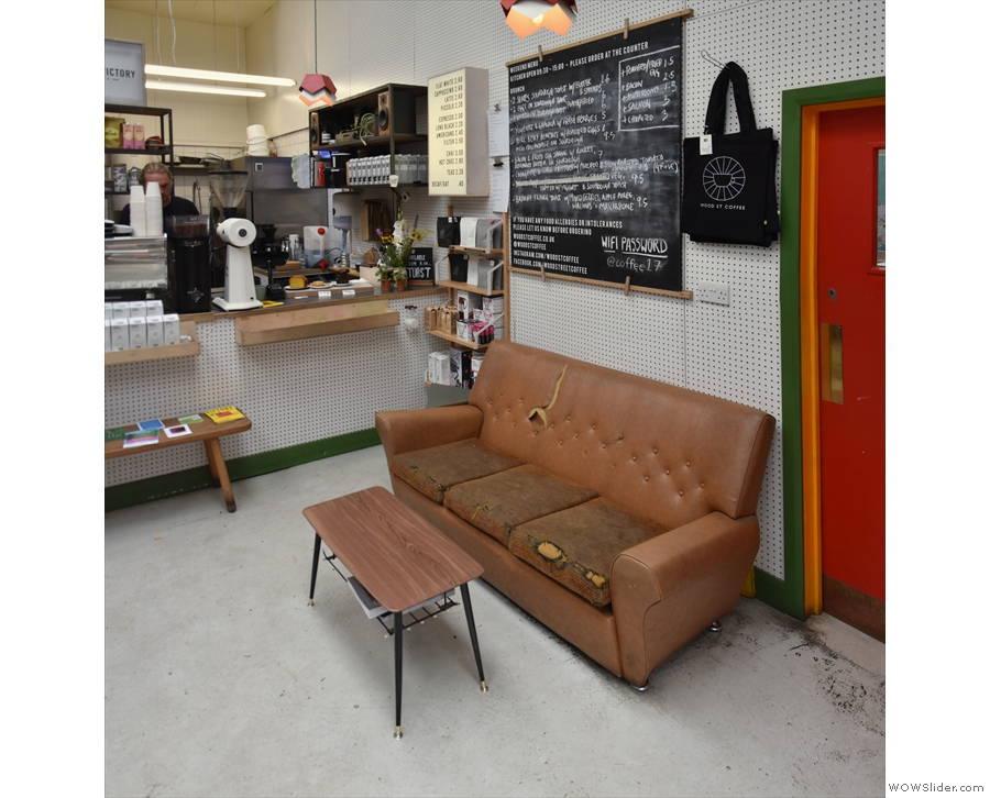 To the right of the counter, under the menu, is a much-loved sofa...
