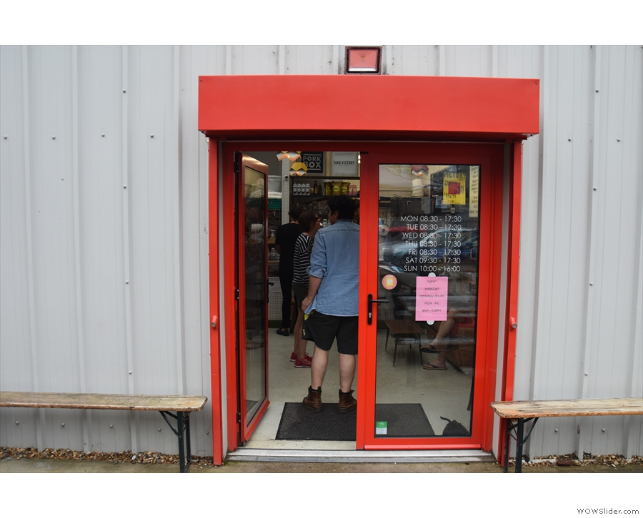 The coffee shop, meanwhile, is accessed via these red-framed double doors, which are...