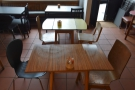 There's a row of three tables down the middle, ending with the one in the window...