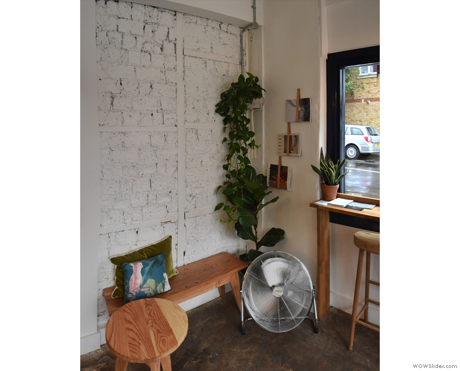 There's a short bench with a stool as a coffee table against the wall...
