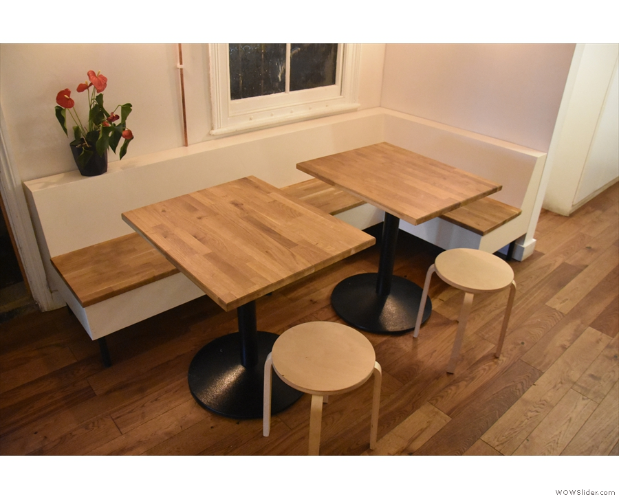 Opposite this, on the left-hand wall, is an L-shaped bench, with two tables and low stools.