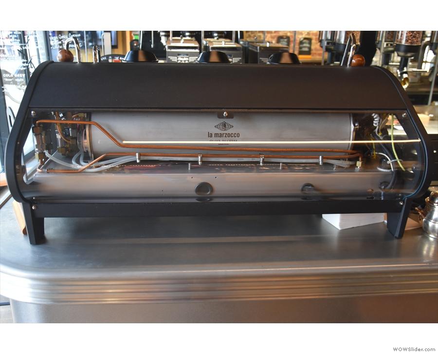 The counter has a three-group La Marzocco Strada espresso machine at the front...