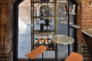 ... followed by a small, two-person table next to a smaller, arched window at the back.