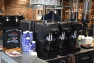 The grinders, meanwhile, are on the wall behind the espresso machine...