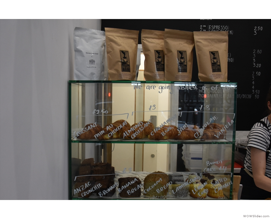 There are cakes and retail bags of coffee for sale off to the left.