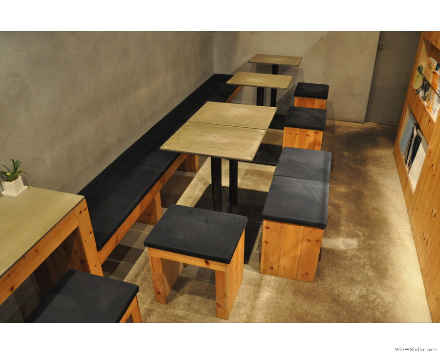 ... while beyond that are four more square two-person tables against another bench.