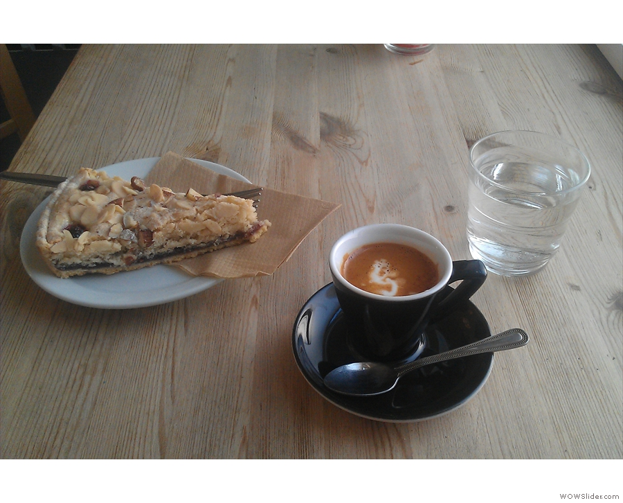 Et, voilà! Bakewell Tart, macchiato and a glass of water.