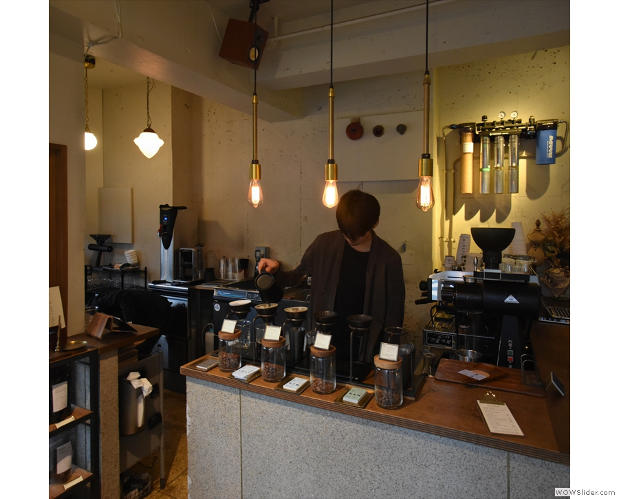 The counter, with its row of V60s and coffee beans in jars, is opposite the door.