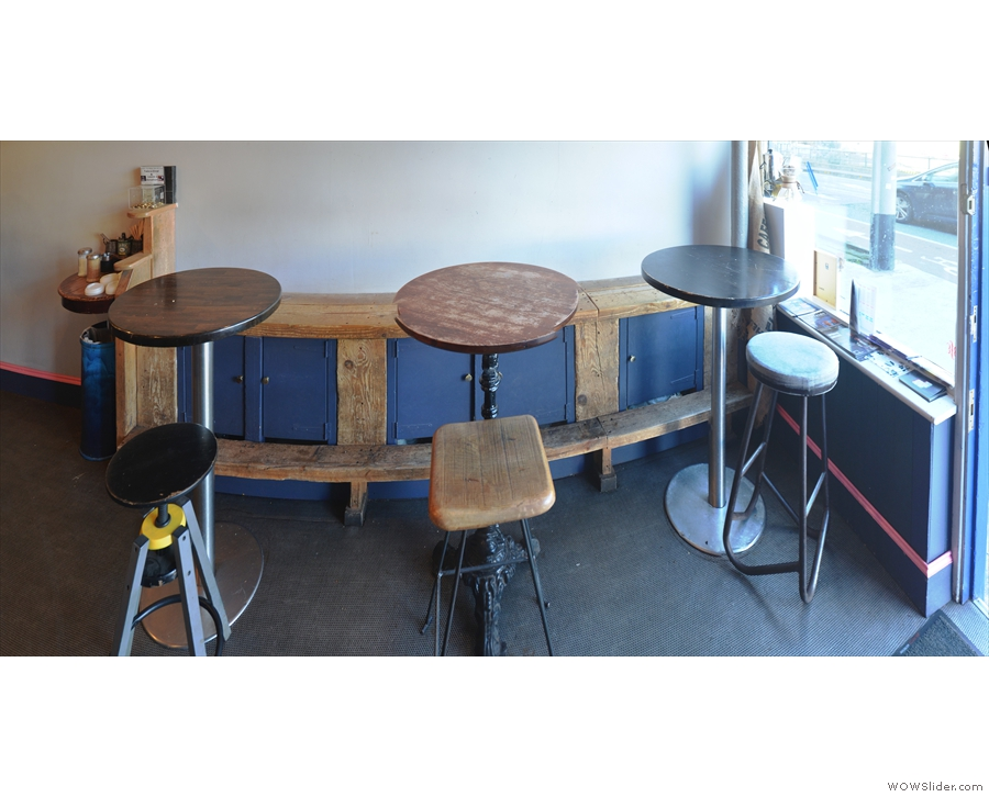 The tables, seen here head-on, with their mis-matching stools.