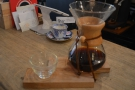 The coffee is served in the Chemex, on a wooden tray, glass on the side.