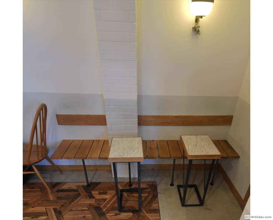 The seating starts at the front with a wooden bench and two small tables.