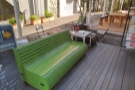 ... facing the covered seating area, where there's this three-person wooden sofa...
