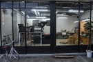 The new roaster, a 22 kg Probat, is clearly visible through the roastery windows...