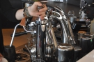 While the espresso extracts, the barista steams the milk.