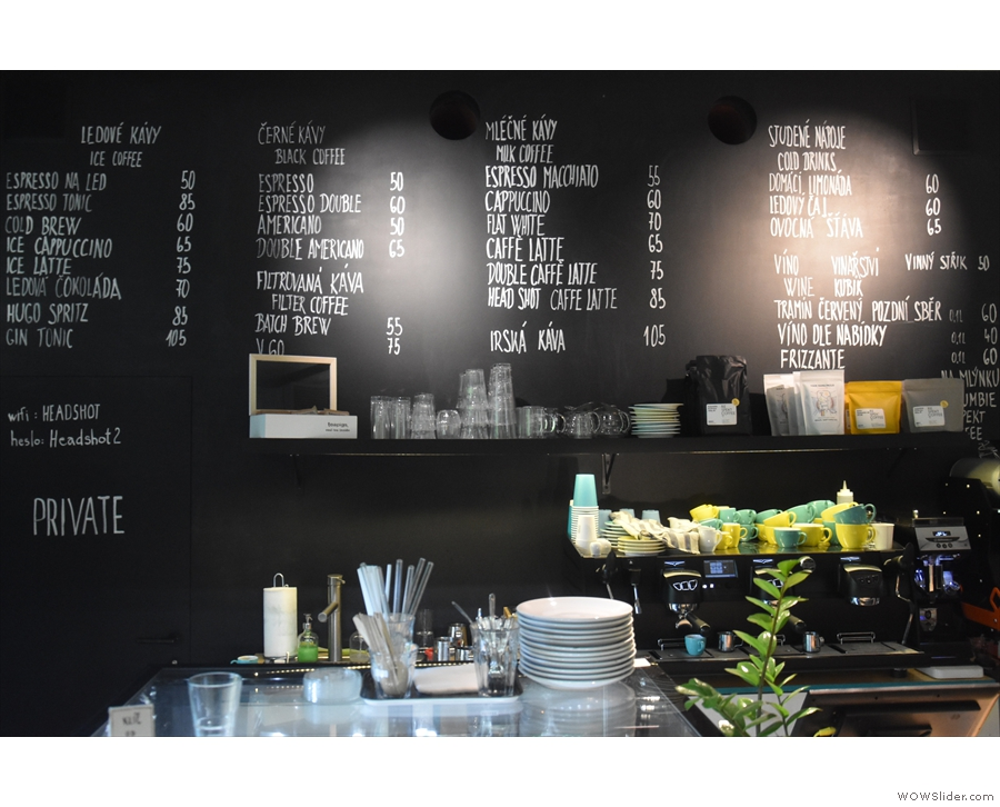 The menu, meanwhile, is on the wall behind the counter, the coffee arranged in columns...