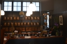 Beyond the L-shaped wooden counter are jars and jars of coffee...