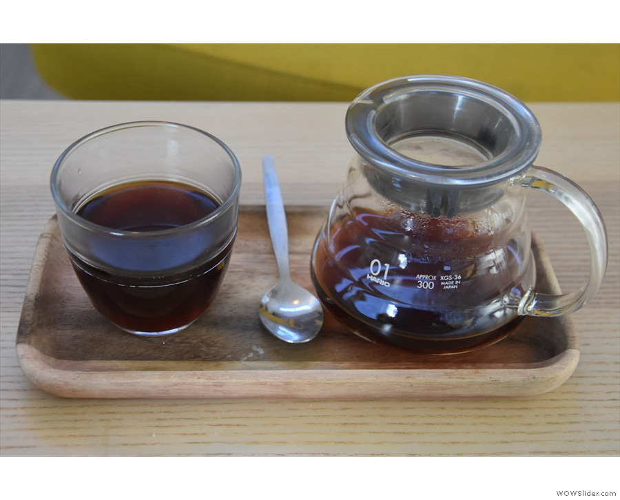 ... served in a carafe on a small wooden tray, with a glass on the side.