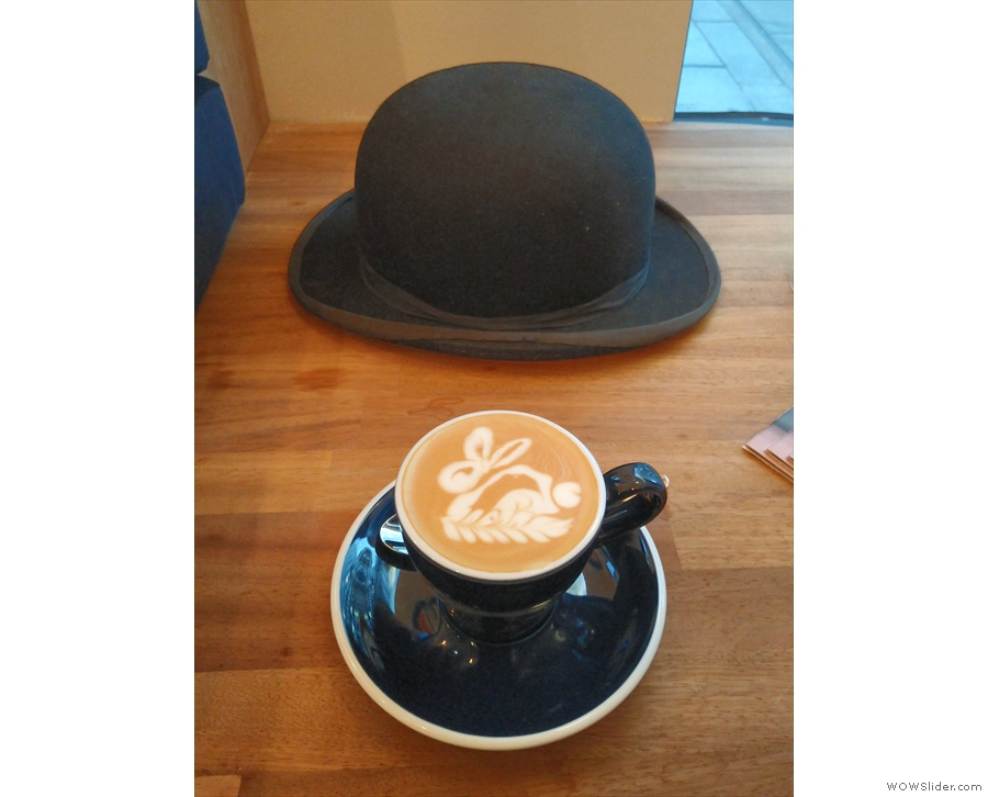 My flat white, with an obligatory hat in the background (sadly not a top hat!).