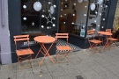 There's a pair of orange, two-person tables, one in front of each window.