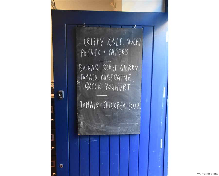 The salad choices and the soup are on a chalk board hanging on the door.