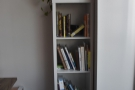 Meanwhile, right at the front by the window, is this narrrow, well-stocked bookshelf.