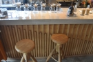 There are a pair of stools by the counter, next to the pour-over station.