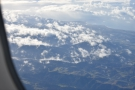 ... flying over the cloud-wreathed mountains which were now far below.