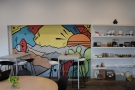 ... while beyond that are two, tall, four-person tables by a mural on the back wall.