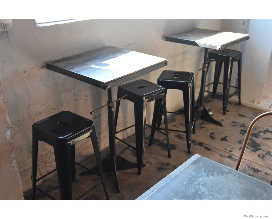 ... beyond which, under the solitary window in the wall, are a pair of two-person tables...