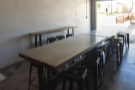 Just inside the door are two long, tall communal tables with stools (seating 16 in all)...