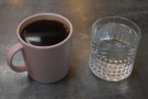 After the coffee has filtered through, it's served in a mug along with a glass of water.