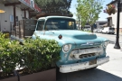 There's an old Chevy truck parked on the corner of San Pedro and Saint John Streets.