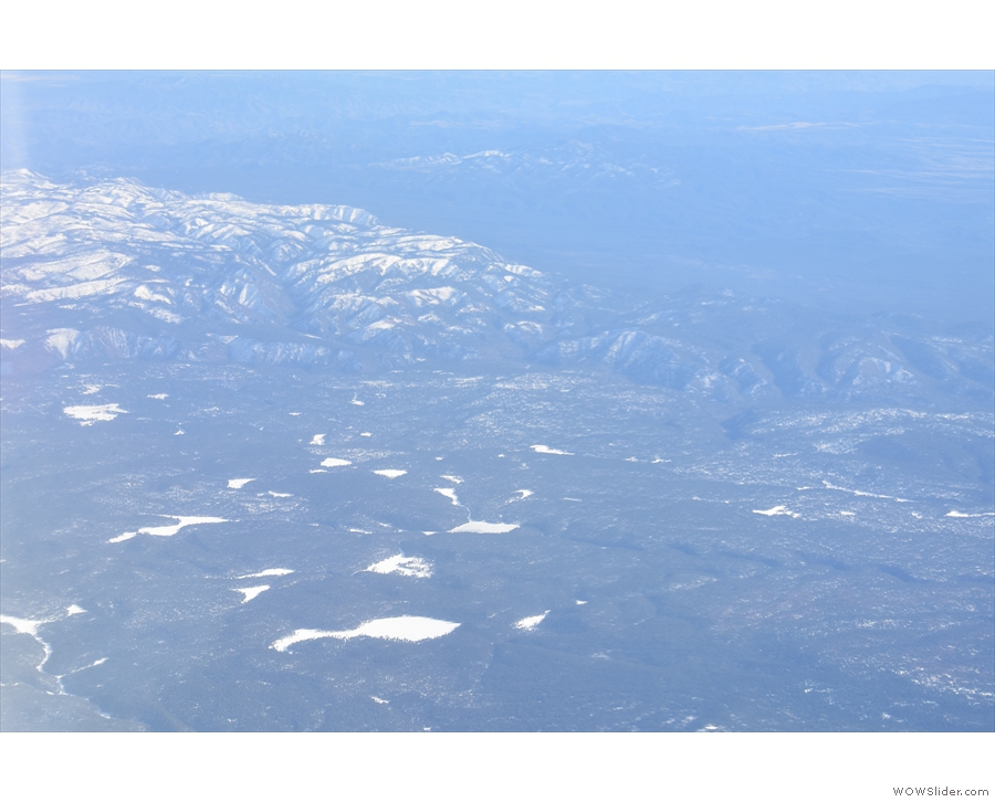 The snow becomes more prevelant on the mountain peaks to the south...