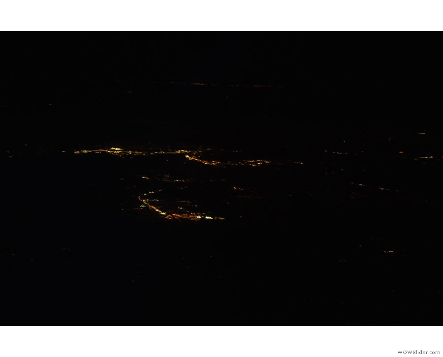 The clouds had cleared and I could see the lights of various towns below us.