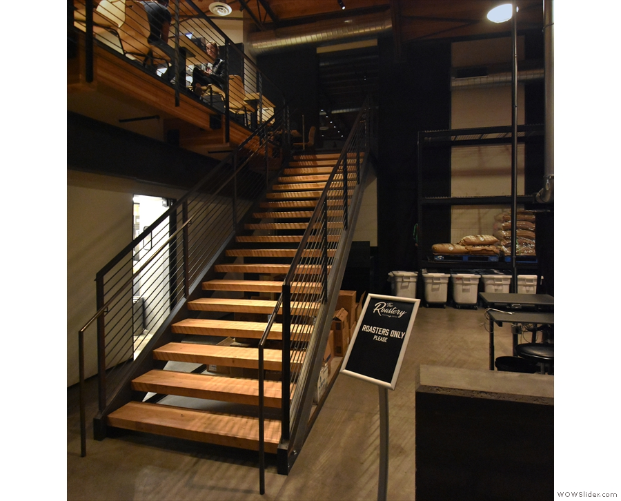 The stairs are at the back of the mezzanine, between it and the roastery.