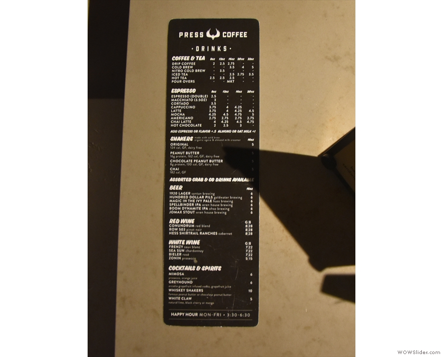 Although the menu is on the girder above, there's a printed menu on the counter top.